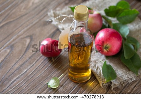 Apple cider vinegar in a glass bottle with fresh apples on a wooden table. Copy space for your text.