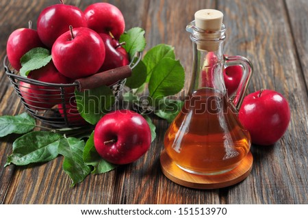 Apple cider vinegar in glass bottle and basket with fresh apples - stock photo