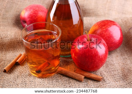 Apple cider with cinnamon sticks and fresh apples on sackcloth background - stock photo