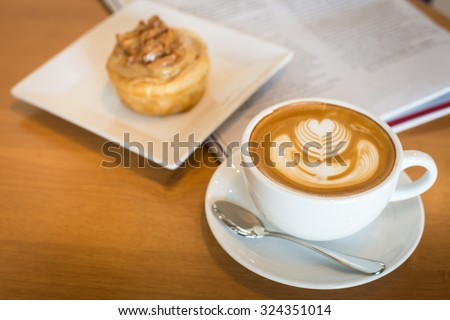 Apple cinnamon roll served with latte art coffee and newspaper on the table at restaurant  - stock photo