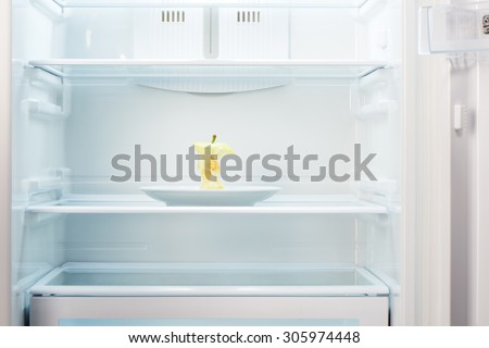 Apple core on white plate in open empty refrigerator. Weight loss diet concept.