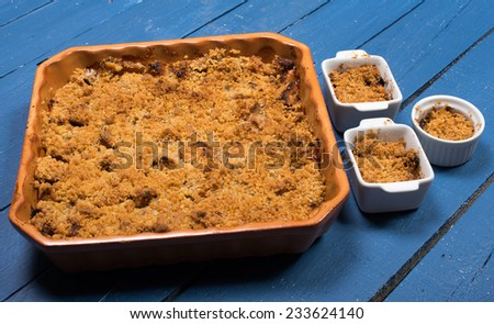 apple crumble on a blue wooden table - stock photo