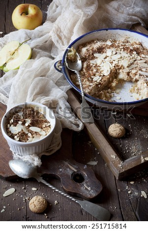 apple crumble with almonds on rustic table with wood frames, apples and cloth - stock photo