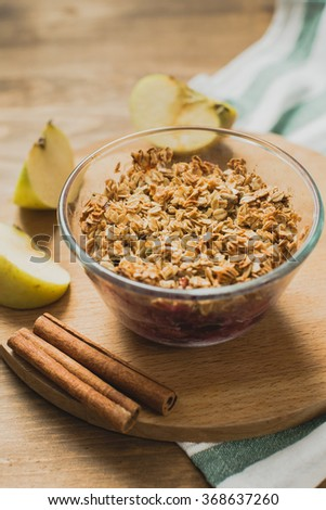 Apple Crumble with oat flakes, cinnamon and berries in glass bowl - stock photo
