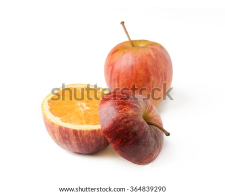 Apple cut with orange inside GMO concept genetically modified fruit - stock photo