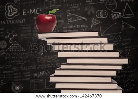 Apple education symbol and stack of books in classroom with written board - stock photo