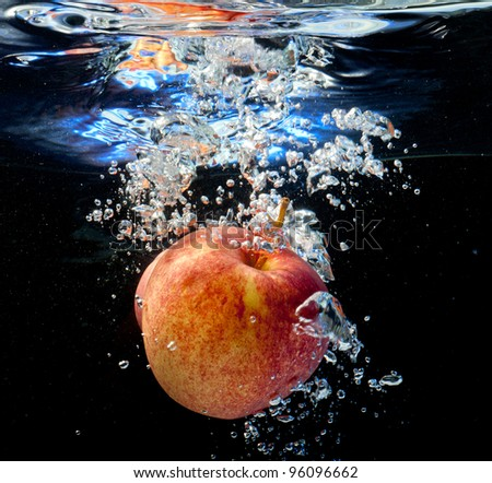 apple fell into the water by raising bubbles. On a black background - stock photo