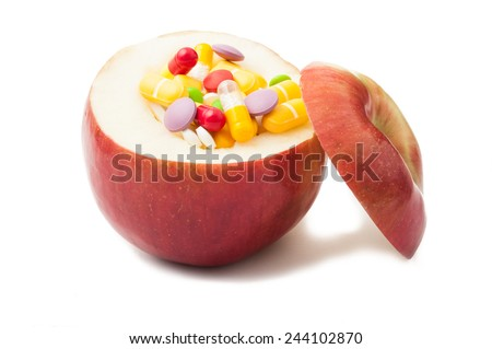Apple filled with different color pills isolated on white and with the  top placed on it�¢??s side - stock photo