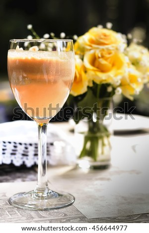 Apple fresh juice served in vine glass and vase with yellow roses on background