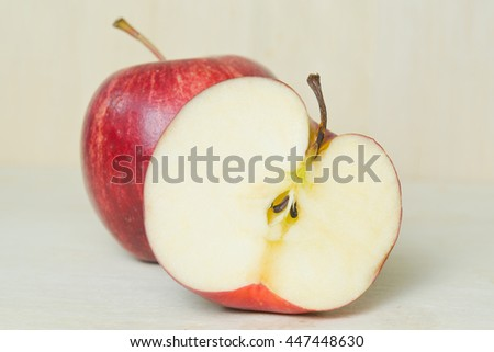 Apple fruit (also known as Malus, domestica, pomaceous fruit) close-up view with half cross section isolated on wooden board background