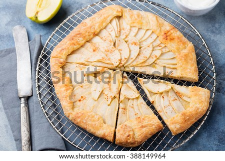 Apple galette, pie, tart with cinnamon on cooling rack  on a blue stone background - stock photo