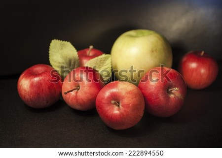 Apple green and red on a black background foliage - stock photo