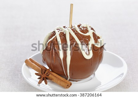 Apple in chocolate on a white plate with cinnamon and anise star - stock photo