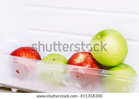 Apple in open empty refrigerator ideal for diet - stock photo