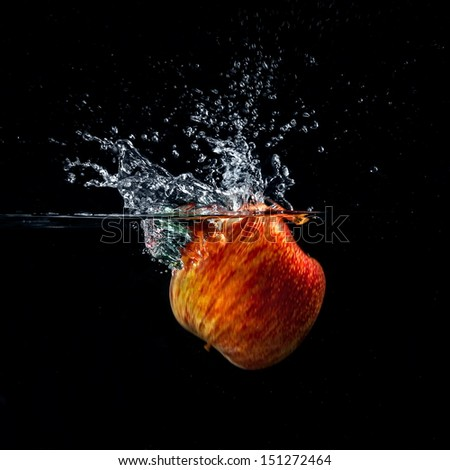 Apple in water on a black background. - stock photo