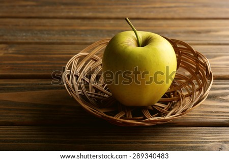 Apple in wicker basket on wooden background