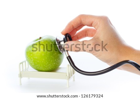Apple is examined with stethoscope in hospital bed - stock photo