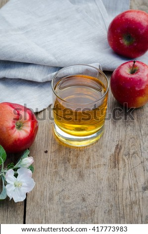 Apple juice and apples (red and green) on a wooden table with a gray tablecloth