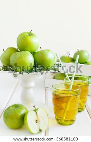 Apple juice from green apples on a white wooden background - stock photo