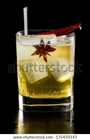 apple juice served in a square glass garnished with a cinnamon stick and an anise star isolated on black