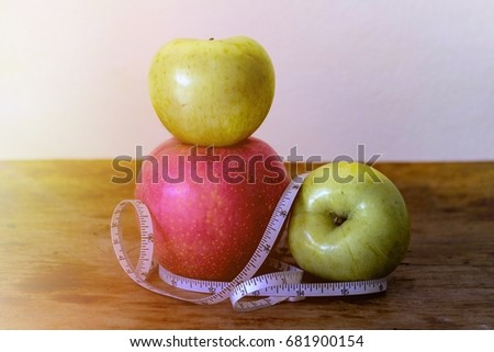 Apple laid on a wooden floor with a waist line wrapped around the apples.