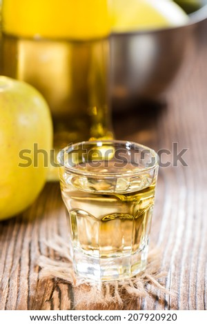 Apple Liqueur Shot (close-up shot) on dark wooden background - stock photo