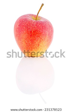 Apple lying on the shiny surface on a white background..