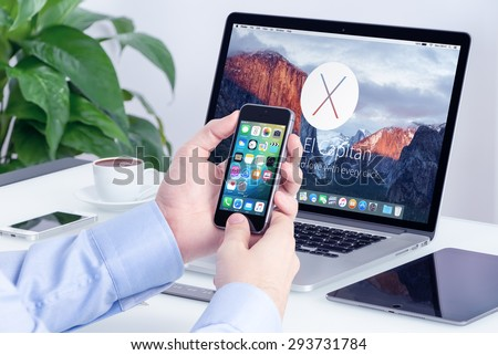 Apple MacBook Pro Retina with announced on WWDC 2015 OS X El Capitan on the screen and Apple iPhone 5s with iOS 9 on the display in male hands in office workspace. Varna, Bulgaria - May 29, 2015. - stock photo