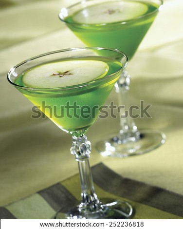 Apple Martini in glasses on green background - stock photo
