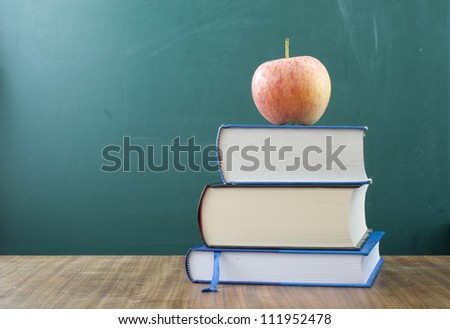 Apple on a pile of books. In the background blank chalkboard. Space for text and graphics. - stock photo