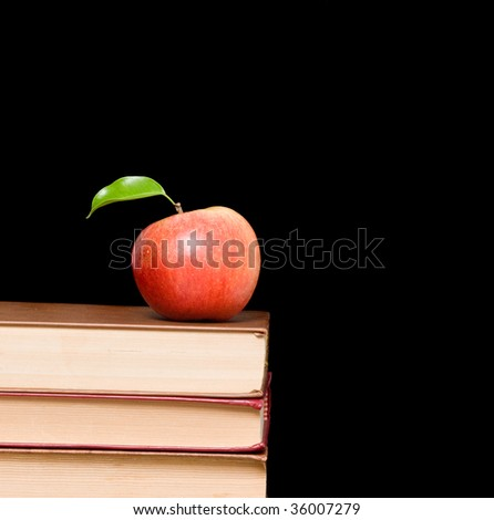 Apple on book isolated on black background
