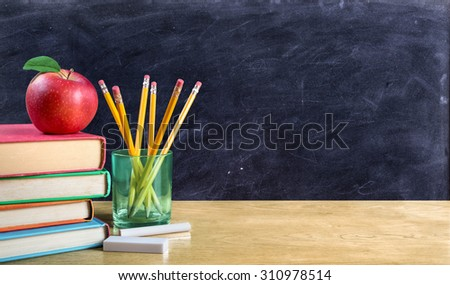 apple on books with pencils and empty blackboard - back to school - stock photo