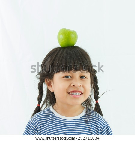 Apple on her head. Cheerful little girl holding a green apple on her head and smiling at camera while standing isolated on white - stock photo