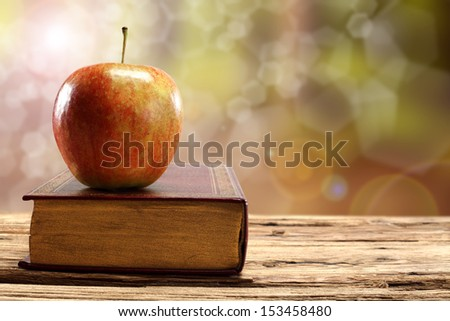 apple on old book  - stock photo