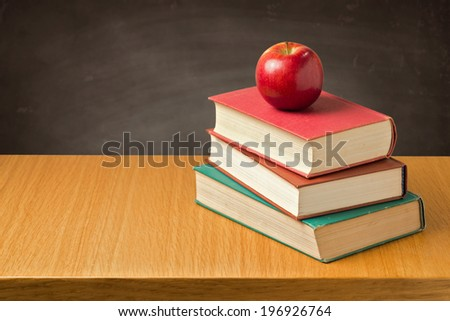 Apple on old vintage books over chalkboard. Back to school concept - stock photo