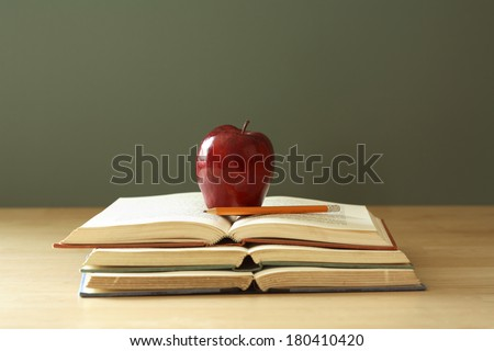apple on stack of open books with pencil  - stock photo
