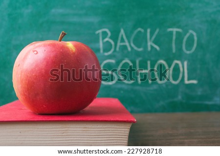 Apple on the book and Back to School handwritten on the chalkboard in the background - stock photo