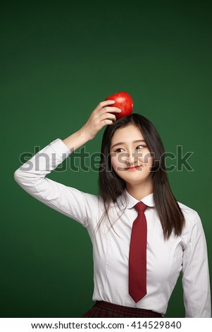 apple on the head of the young student - stock photo