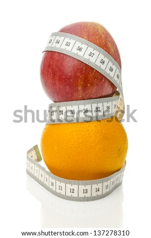 Apple on top of orange wrapped with measuring tape. Weight loss concept. - stock photo