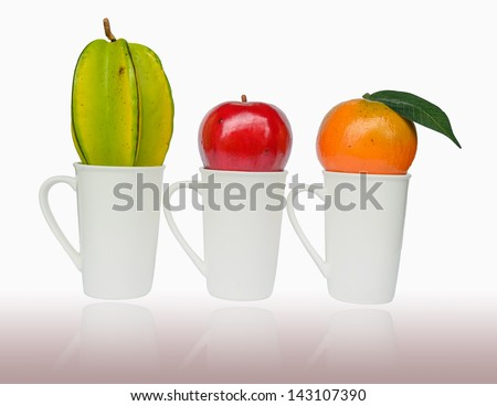 Apple, Orenge and Carambola put on the cup isolated on white