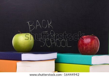 apple over a stack of books next to a chalkboard