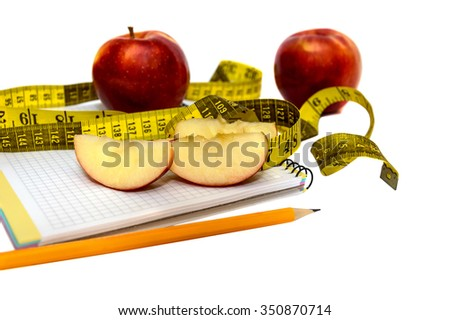 Apple, pencil and measuring tape on notepad isolated on white