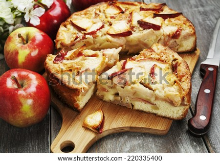 Apple pie and red apples on a wooden table - stock photo