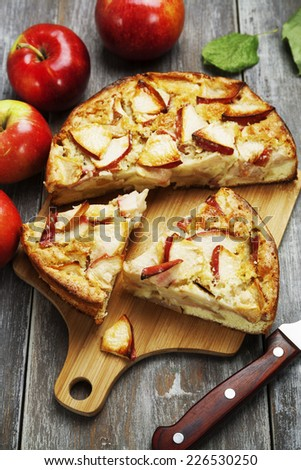Apple pie and red apples on a wooden table