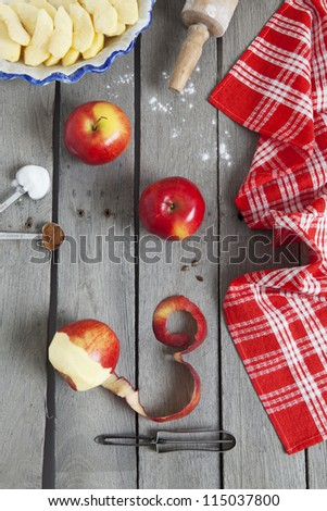 Apple pie ingredients on a raw, weathered wood background.