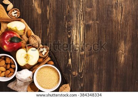 Apple pie ingredients over brown wooden background. Baking concept - stock photo