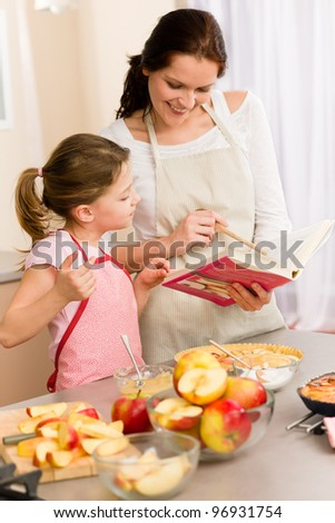 Apple pie mother and daughter follow recipe from baking cookbook - stock photo