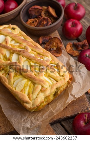 Apple pie on a board with fresh apples
