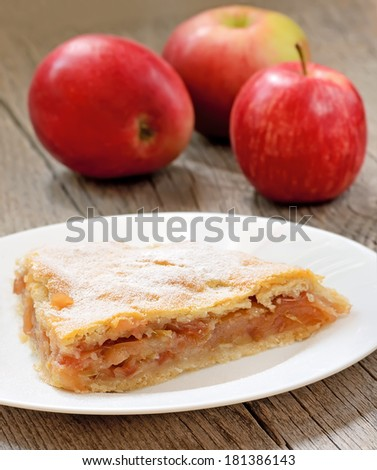 Apple pie on white plate on wooden table