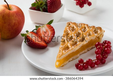 apple pie slice on white plate with currant and strawberries